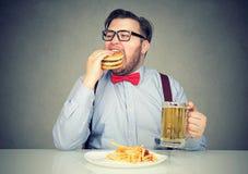 Человек есть пиво высококалорийной вредной пищи выпивая Стоковые Изображения