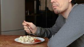 Человек ест вареники при вилка, кладя их в томатный соус в кухне акции видеоматериалы