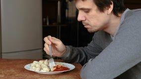 Человек ест вареники при вилка, кладя их в томатный соус в кухне видеоматериал