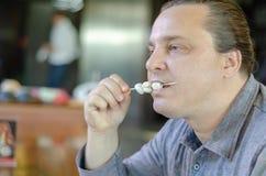 Человек ест сыр на завтраке стоковое изображение