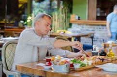 Человек ест турецкий завтрак в ресторане стоковая фотография rf