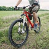 Человек ехать велосипед вдоль проселочной дороги Стоковое Фото