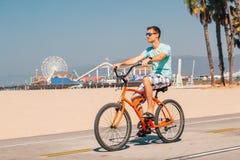 Человек ехать велосипед пляжа около пляжа Венеции в Лос-Анджелесе Стоковая Фотография