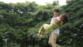 Человек закручивая его девушку в парке сток-видео