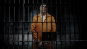 Человек запирается в тюремной камере Пленник с наручником смотрит камеру отснятый видеоматериал 4k акции видеоматериалы