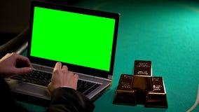 Человек зарабатывая деньги в интернете, золоте в слитках лежа близко, вклады в надежном банке стоковые изображения rf