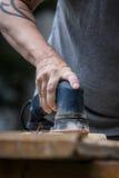 Человек зашкурит деревянную планку Стоковое Изображение RF