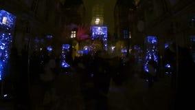 Человек за стеклянной коробкой с плавать оперяется в мигающем светильнике вытягивая гримасы видеоматериал