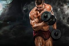 Человек зверского сильного мышечного культуриста атлетический нагнетая вверх мышцы с гантелью на черной предпосылке разминка стоковая фотография