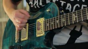 Человек играет зеленую электрическую гитару с концом-вверх сток-видео