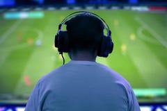Человек играя видеоигру на ноче стоковые фото