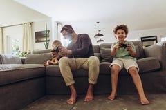 Человек играя видеоигру с его детьми стоковое фото rf