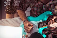 Человек играя голубой конец электрической гитары вверх дома Практикуя гитара и игра сольной уча гитары стоковое изображение rf
