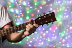 Человек играя на акустической гитаре Пальцы крупного плана на шеи гитары против рождества запачкали света bokeh на предпосылке Стоковые Изображения RF