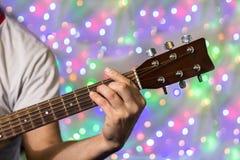 Человек играя на акустической гитаре Пальцы крупного плана на шеи гитары против рождества запачкали света bokeh на предпосылке Стоковая Фотография