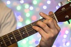 Человек играя на акустической гитаре Пальцы крупного плана на шеи гитары против рождества запачкали света bokeh на предпосылке Стоковое Изображение