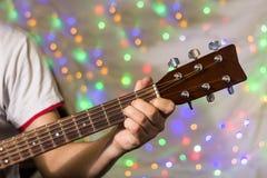 Человек играя на акустической гитаре Пальцы крупного плана на шеи гитары против рождества запачкали света bokeh на предпосылке Стоковое Фото