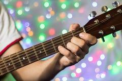 Человек играя на акустической гитаре Пальцы крупного плана на шеи гитары против рождества запачкали света bokeh на предпосылке Стоковые Фото