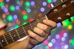 Человек играя на акустической гитаре Пальцы крупного плана на шеи гитары против рождества запачкали света bokeh на предпосылке Стоковые Фотографии RF