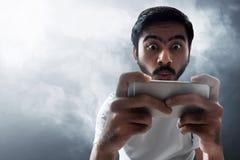 Человек играя передвижные игры на предпосылке дыма стоковое изображение