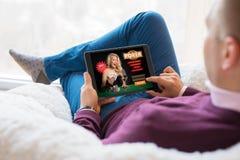 Человек играя покер онлайн на таблетке стоковые изображения rf