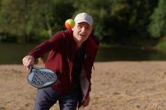Человек играя теннис пляжа Стоковые Изображения