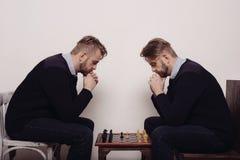 Человек играя шахмат против себя стоковая фотография