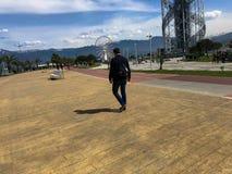 Человек идет вдоль прогулки на улице в тропическом теплом курорте рая на предпосылке зеленых пальм стоковое фото rf
