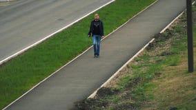 Человек идет вдоль тротуара в городе видеоматериал