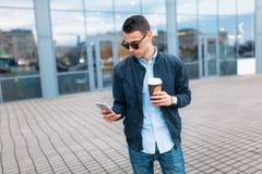 Человек идет вокруг города и выпивая кофе от бумажного стаканчика, красивый парень идет вокруг и отдыхающ, парень на backgrou Стоковое Изображение