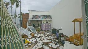 Человек идет о доме с обрушенной крышей после урагана