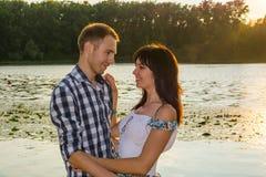 Человек идет расцеловать молодую женщину и обнимает ее на заходе солнца Стоковое Фото