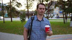 Человек идет через парк города со стеклом кофе в его руке и сумке ноутбука сток-видео