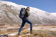 Человек идя в горы с рюкзаком стоковая фотография rf