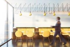 Человек идя в кафе с желтыми софами стоковое фото rf