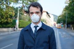 Человек идя в маску предохранения от города нося стоковые фотографии rf