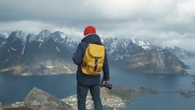 Человек идя на пик горы на заходе солнца в замедленном движении Носить куртку, красную шляпу и желтое backpac r видеоматериал