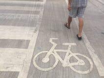 Человек идя около дорожного знака велосипеда стоковая фотография rf