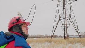 Человек идя отремонтировать кабель электрического напряжения тока к электрической башне сток-видео