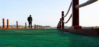 Человек идя самостоятельно на пристань стоковое изображение rf