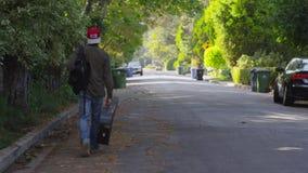 Человек идя с гитарой на улице сток-видео