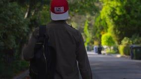 Человек идя с гитарой на улице видеоматериал