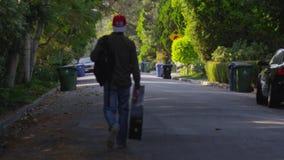 Человек идя с гитарой на улице акции видеоматериалы