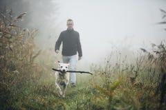 Человек идя с собакой в тумане осени стоковая фотография