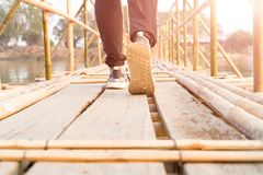 человек идя, человек успеха путешественника идя к успеху на длинном деревянном бамбуковом мосте Стоковые Фото