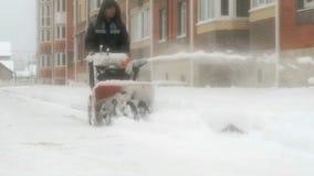 Человек извлекая снег с машиной плужка снега акции видеоматериалы