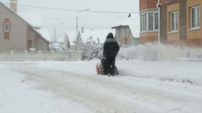 Человек извлекая снег с машиной плужка снега видеоматериал