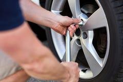 Человек изменяет автошину на его автомобиле стоковая фотография rf