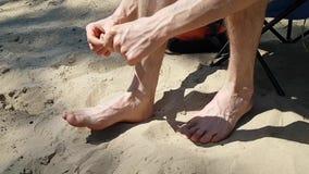 Человек или подросток связывают рану тесьмой на его большом пальце ноги Ушибите идя на песок на пляже Прибрежное загрязнение видеоматериал