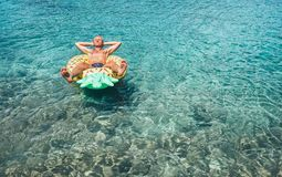 Человек имеет ослабить время когда заплывы на раздувном бассейне ананаса звенят Стоковые Изображения